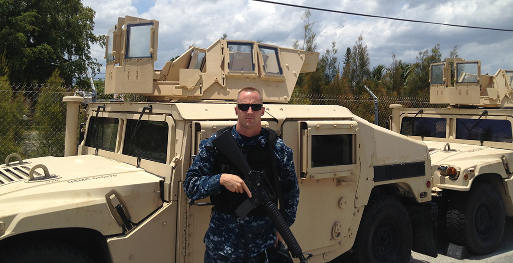 man in front of humvee holding gun